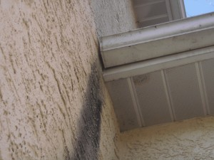 Staining on stucco from water flowing past the end of the rain gutter